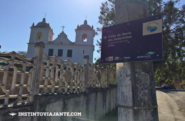 Igreja de São Sebastião de Itaipu e a placa informando para seguir pela direita, entrando na rua da Amizade.