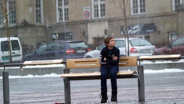 Menino com frio sentado em um banco