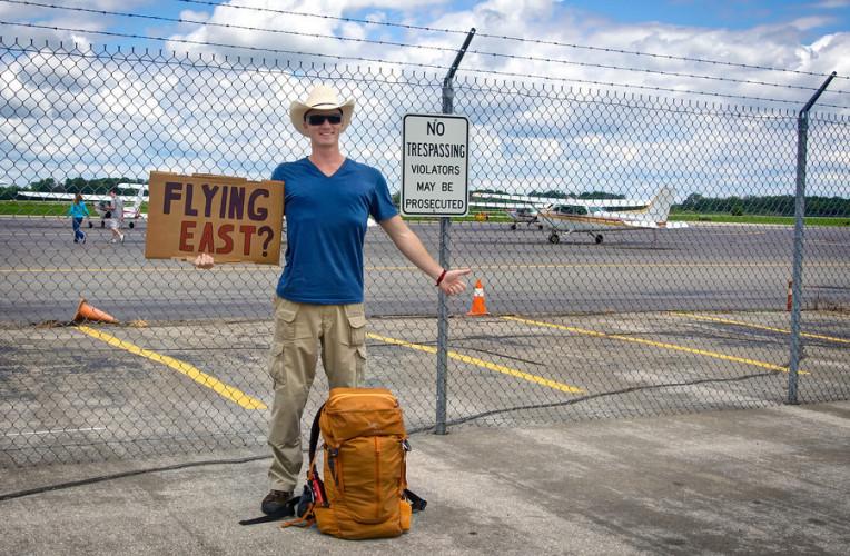 Homem pedindo carona no aeroporto